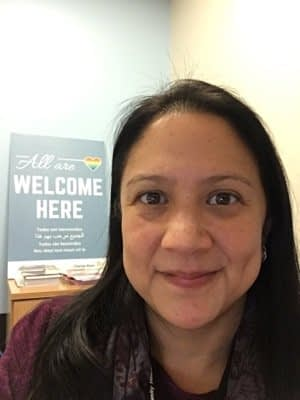 """Portrait photo of woman smiling with sign in background saying """"All are welcome here"""""""