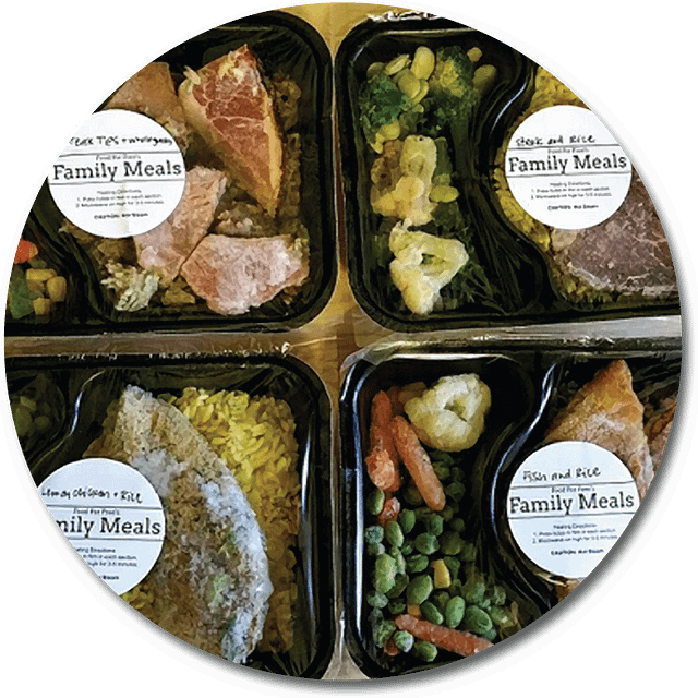 photo of four different meal combos each in black trays and each with a white round label on it